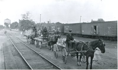 Fruit harvest in Glover baskets, loaded on horse-drawn wagons waiting for the fruit train at  the Burlington GTR Station in Freeman, ca 1920