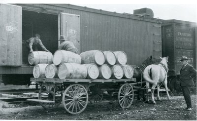 Barrels of apples being loaded into a refrigerated boxcar at Freeman Station, ca 1920