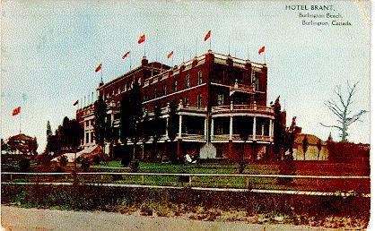 Hotel Brant, Burlington Beach, Burlington, Canada -- Exterior, east end with flags; postmarked May 18, 1910