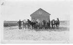 Art Brame and 8 draft horses with a frame building, Saskatchewan, 1923