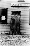 An outhouse set in front of the door to the Gazette Printing Office, now 370 Brant Street, as a Hallowe'en prank, ca 1910