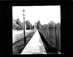 Sidewalk, fence and street lamp, downtown Burlington ca 1900