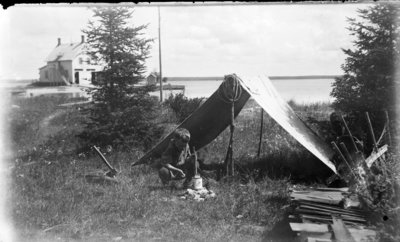 "Middle Island:  Donald Hartlep ""Camping"" with Boathouse in Background"