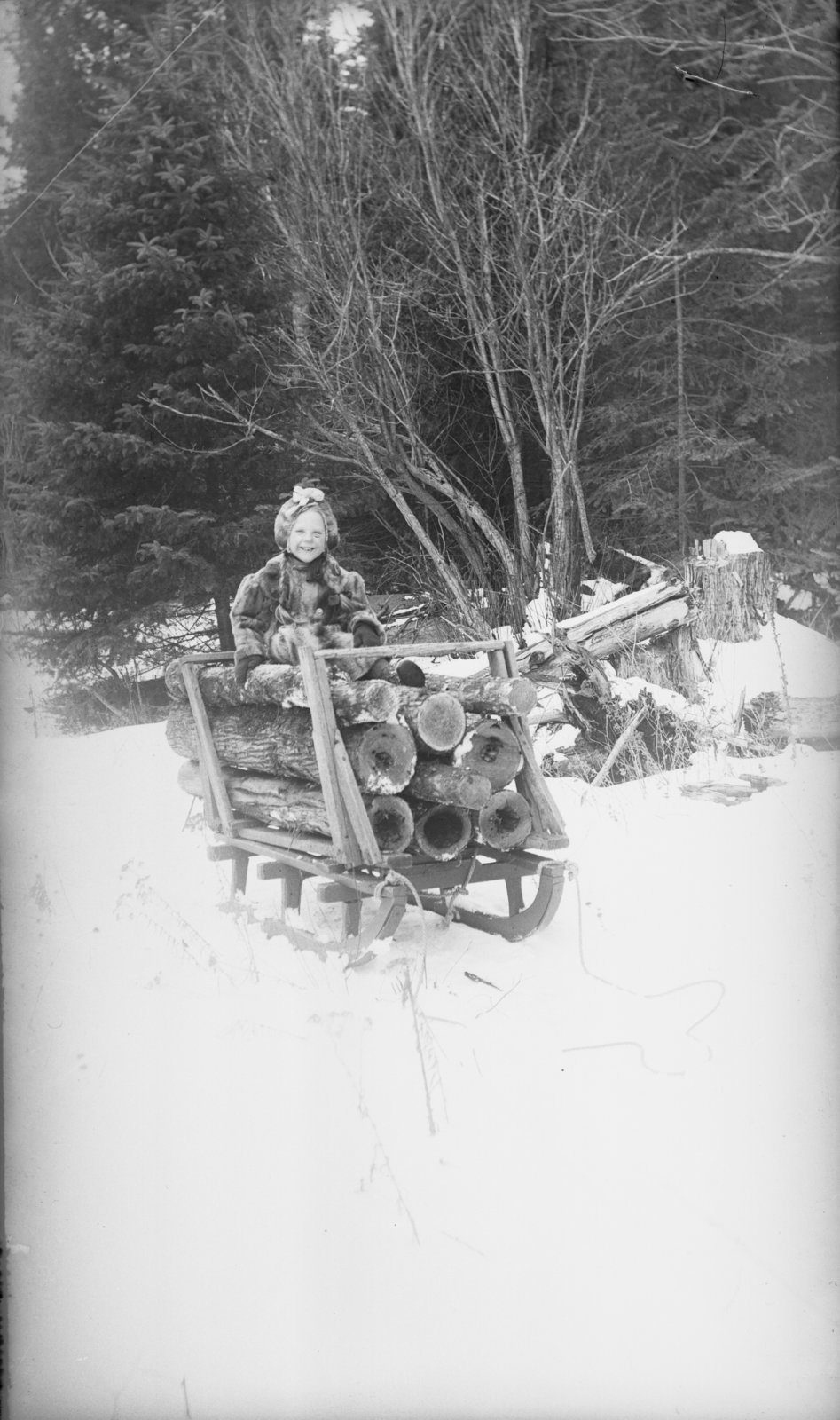 Middle Island: Esther Hartlep sitting on small sleigh of logs.