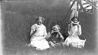 Middle Island:  Esther Hartlep (middle) with two unidentified girls eating watermelon in summer.