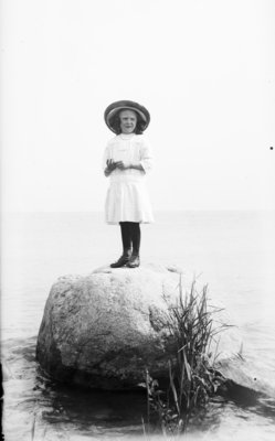 Middle Island:  Esther Hartlep standing on big rock near shore of Lake Huron.