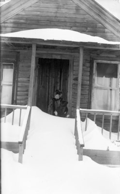 Middle Island:  Esther Hartlep with stuffed bear on snow-drifted porch of dwelling.