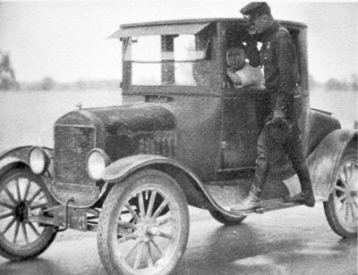 Michigan State Police Trooper checking a driver and automobile, c 1920s