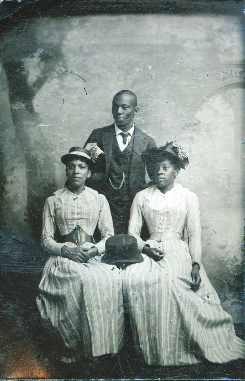 A small tintype of three unidentified individuals, two women, seated, and a young Black gentleman, standing. The date, location and name of the photographer are unknown. Courtesy the Brock University James A. Gibson Special Collections & Archives.