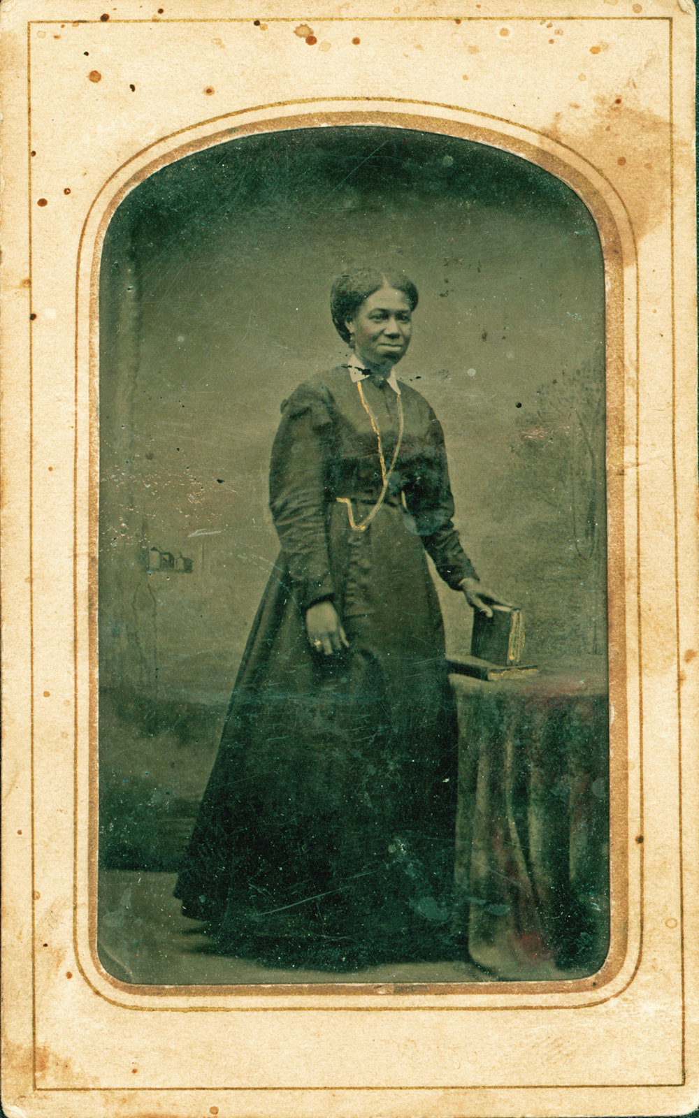A woman standing with a book beside a table covered with a decorative cloth is featured in this small black and white tintype photograph. Courtesy the Brock University James A. Gibson Special Collections & Archives.