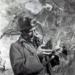 Photograph of miner observing rock underground