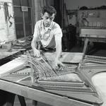 Photo of a worker attaching piano strings