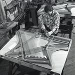 Photo of a worker tightening piano strings