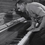 Photo of a worker examinging a pianos internal mechanisms