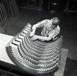 Photograph of man working on engine part in factory