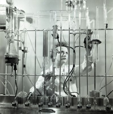 Photograph of woman in lab coat using vacuum fusion gas analysis apparatus