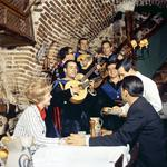 Photograph of a group of men playing guitar for a couple