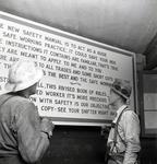 Photograph of two miners reading a sign