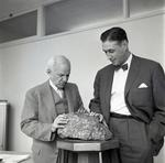 Photograph of two men with a rock sample