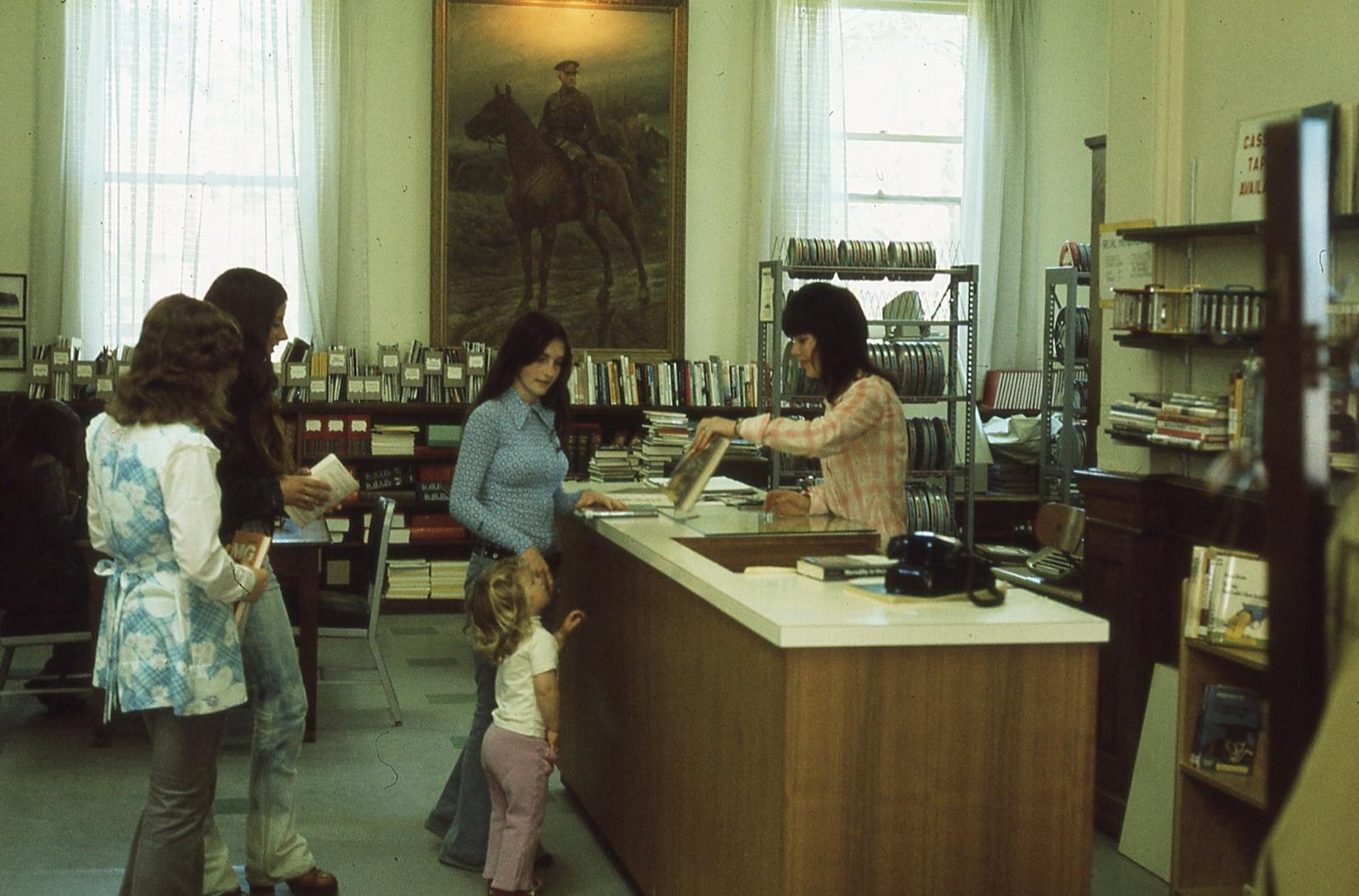 Interior of Carnegie library, checkout desk and film department, 1975