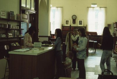 Interior of Carnegie library, checkout desk and reference department, 1973