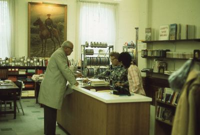 Interior of Carnegie library, checkout desk, reference and film department, 1975