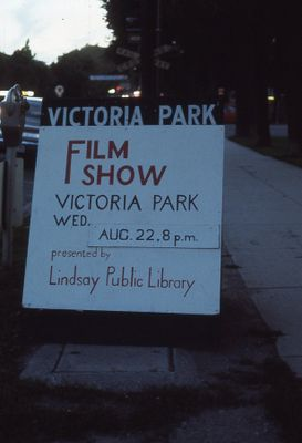 Sign advertising outdoor film showing, a library program, 1973