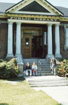 Exterior of Carnegie library, patrons on front steps, 1973