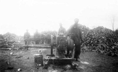 Groupe d'hommes avec un moteur à essence actionnant une scie.