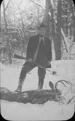 Full-length portrait of a hunter with a slain stag at this feet