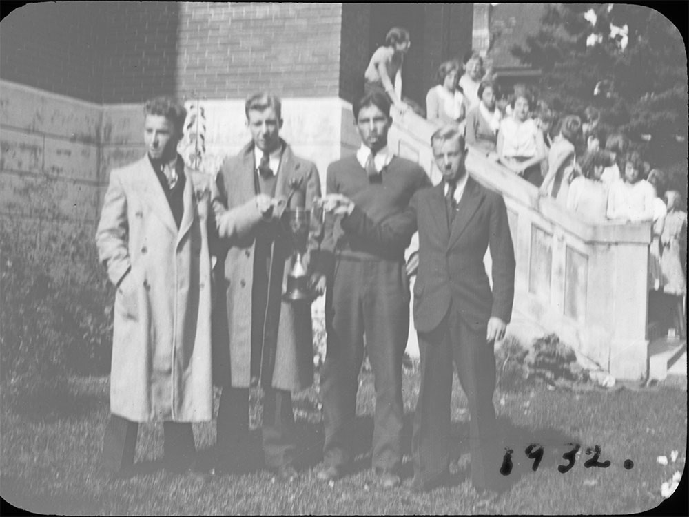 Portrait of a group of young men including Jack Armstrong and Bill Griffis in front of Colborne High School holding a trophy