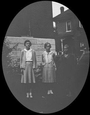 Portrait of three young women in front of Colborne High School