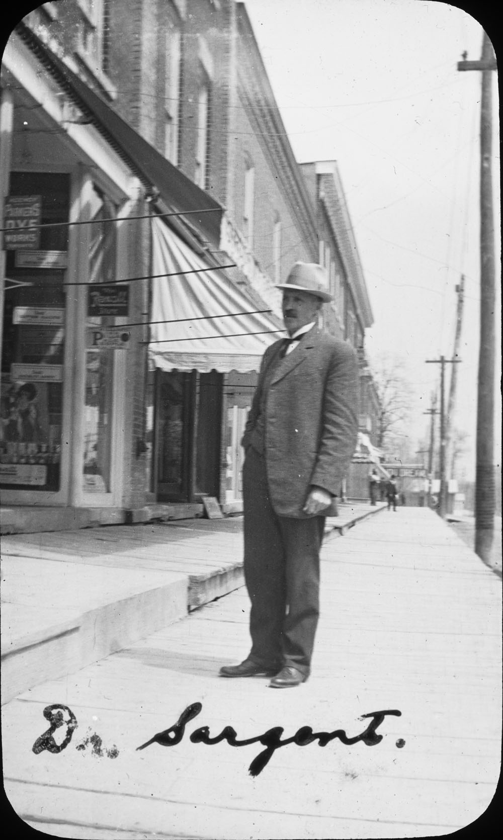 Photograph of Dr. W.A. Sargent on a King Street East wooden sidewalk, Colborne, Cramahe Township