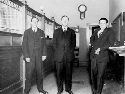 Three bank employees standing inside a bank, Colborne