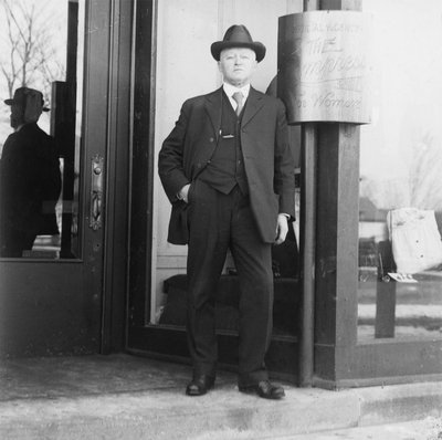 Scougale of Scougale Brothers Ladies Wear standing on the steps of his storefront, Colborne