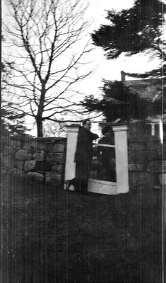 Two people standing at the gate of a stone wall fence