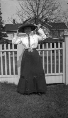 Woman posing in front of a home
