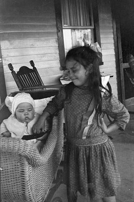 Young girl with a baby in a carriage on the porch of the Griffis' summer house