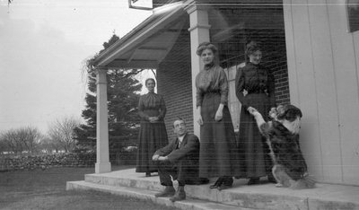 Three women, a man and a dog on a porch
