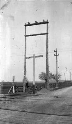 Man sitting on a fence at a railway crossing