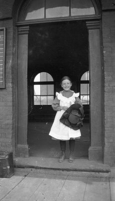 A young girl holding her hat in the doorway of the Grand Truck Railroad Station