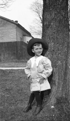 A young boy posing under a tree