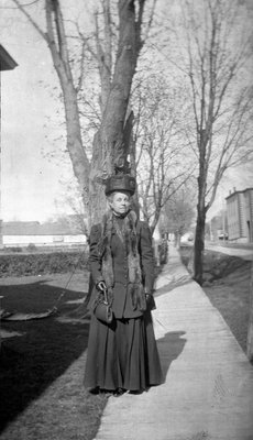 A woman standing on a Church St. West wooden sidewalk, Colborne