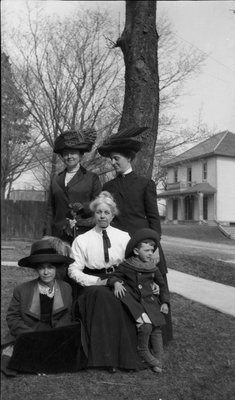Four women and a young boy posing outside