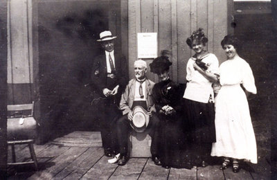 Reproduction photograph, John Monroe Black, George I. Merriman, Ella Jane (Merriman) Black, unidentified young woman, and Hattie Edna (Black) Kerr at the Grand Trunk Railway Station / Canadian National Railway Station, Colborne