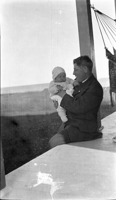 Father and child on the porch of the Griffis' summer house