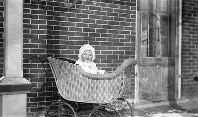 Baby in a wicker carriage on the Griffis? house porch