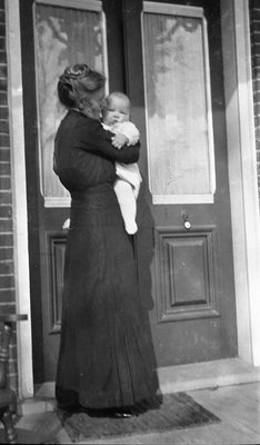 Griffis family photo of a woman and baby standing at a front door