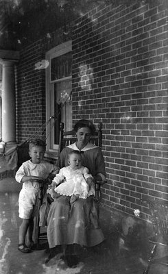 Griffis family photo of a mother, a child, and baby on a porch