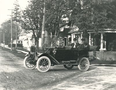 Photograph of a young boy driving two men, Chief Jamieson and possibly Frank Griffis, in a 1910s car, Colborne, Cramahe Township